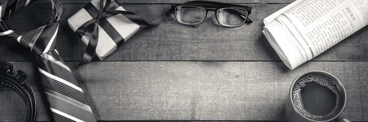 Tie, Belt, And Gift Box With Reading Glasses, Newspapers, And Coffee On Wooden Table - Fathers Day Concept Banner