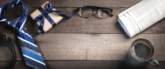 Tie, Belt, And Gift Box With Reading Glasses, Newspapers, And Coffee On Wooden Table - Fathers Day Concept