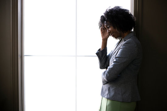 Silhouette of a stressed out black African American businesswoman looking worried and thinking about problems and failure by the office window.  She looks depressed or upset about debt or bankruptcy.