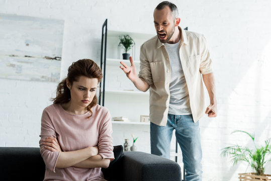 angry man screaming near upset woman with crossed arms