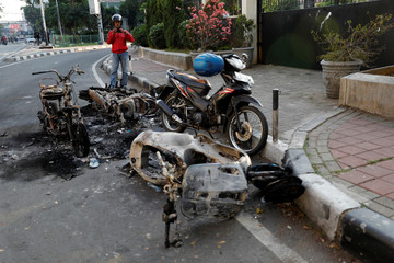 Man takes pictures of damaged motorbikes burned after a riot following the announcement of presidential election results in Jakarta
