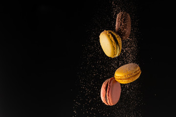 Poster Macarons Colored macaroons, French cookies, colored levitates with cocoa powder on a black background