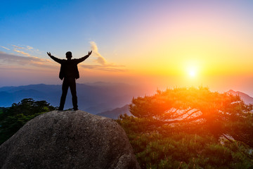 Hiker is standing on a rock with raised hands and enjoying sunrise Wall mural