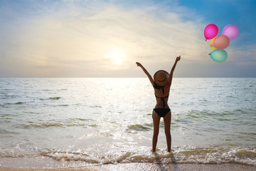 happiness on holiday back view image of young asian beautiful and sexy girl in black bikini who standing and holding balloons colored and raise hand up with happy and smile face on summer vacation.