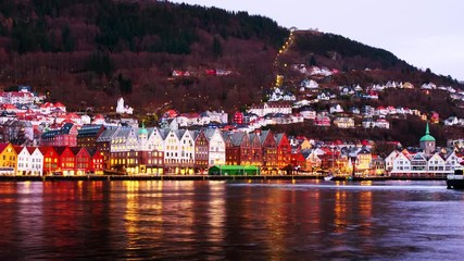 Wall Mural - Bergen, Norway. View of harbour old town Bryggen in Bergen, Norway in the evening. Famous landmarks at sunset. Time-lapse with car traffic and boats, zoom in