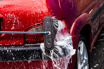 manual car washing with pressurized water and soap in car wash outdoor