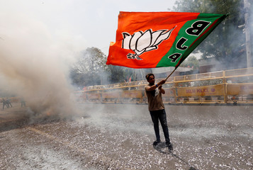 A BJP supporter waves a party flag as he celebrates after learning the initial election results, in New Delhi