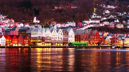 Wall Mural - Bergen, Norway. View of harbour old town Bryggen in Bergen, Norway in the evening. Famous landmarks at sunset. Time-lapse with car traffic and boats, pan