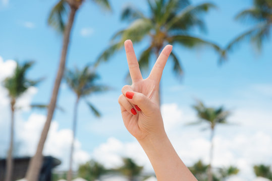 Woman's hand with two fingers up in the peace or victory symbol. Also the sign for the letter V in sign language. Beach rest against the backdrop of summer water