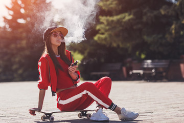 Vaping girl. Young woman sitting on skateboard and vape e-cig. Pretty young female in black hat, red clothing vape ecig, vaping device at the sunset. Toned image. Hip-hop style.