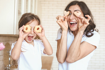 Happy mother and daughter with tasty cookies having fun in kitchen at home
