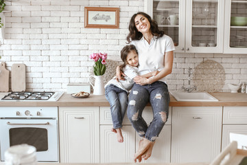 Happy mother with daughter in kitchen at home