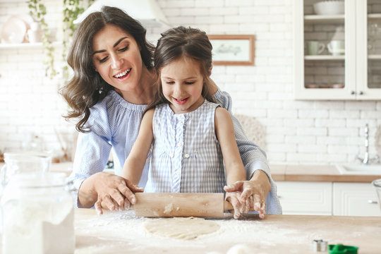 Happy mother with daughter preparing cookies in kitchen at home