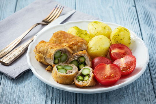 Roasted asparagus stuffed pork tenderloin served with potatoes and tomatoes.