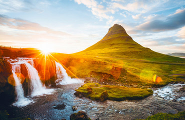 An epic sunset with Kirkjufellsfoss waterfall. Location Iceland, Europe.