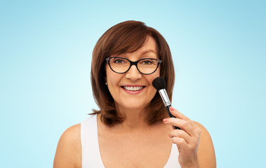 beauty, make up and old people concept - smiling senior woman with blush brush over blue background