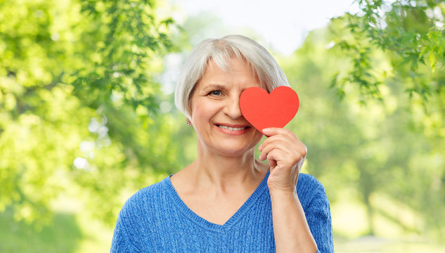 valentine's day, summer and old people concept - portrait of smiling senior woman covering one eye with red heart over green natural background