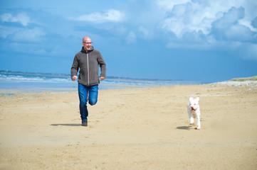 Mann läuft mit seinem Hund an Sandtrand