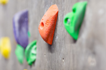 fitness, extreme sport, bouldering, people and healthy lifestyle concept - close up of rock holder on indoor climbing wall Wall mural