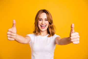 Close up photo beautiful pretty she her foxy lady hold arms hands thumb fingers up short hairstyle amazed excited advising buy buyer new product wear casual white t-shirt isolated yellow background