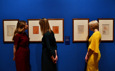 Royal Collection Trust staff pose beside preparatory sketches of Leonardo Da Vinci's The Last Supper at A Life in Drawing an exhibition in London