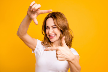 Close up photo beautiful amazing she her foxy lady overjoyed hold arms hands fingers pretend focus photographer creative mind winking eye wear casual white t-shirt isolated yellow background