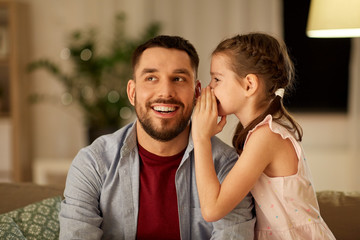 family, fatherhood, leisure and people concept - happy daughter whispering secret to father at home in evening