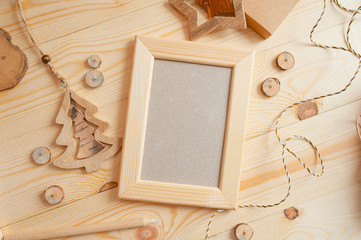 Christmas light wooden frame for photo on a wooden background with rope and wooden toys. Flat lay, top view photo mockup