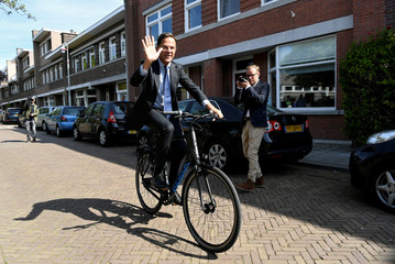 Dutch Prime Minister Mark Rutte of the People's Party for Freedom and Democracy leaves a polling station on bike after voting for the European elections, in The Hague