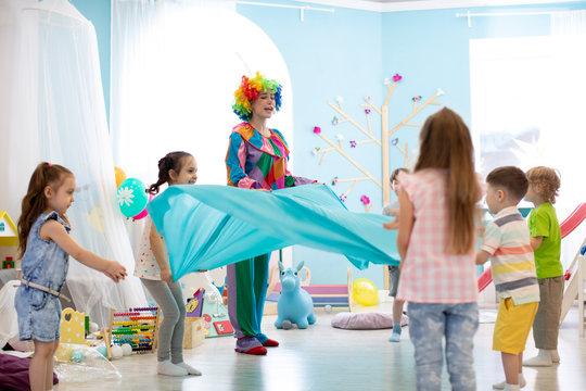 Children group have fun on birthday party. Clown entertains kids