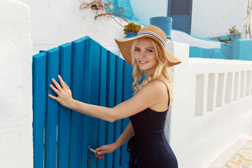 blond woman in a blue jump suit and a sun hat, about to enter a blue painted wooden front gate in Oia on Santorini