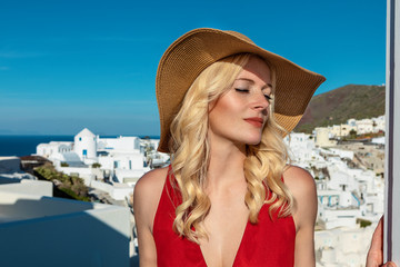 blond woman in a red dress and a sun hat in Oia on Santorini, enjoying the warm sun