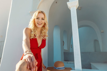 blond woman in a red dress, standing on stairs with her husband holding her hand with Oia on Santorini in the background