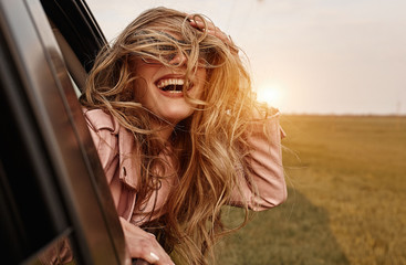 Happy young smilling woman enjoying nature traveling in a car and looking out.