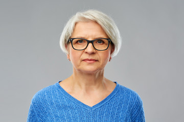 vision and old people concept - portrait of senior woman in glasses over grey background