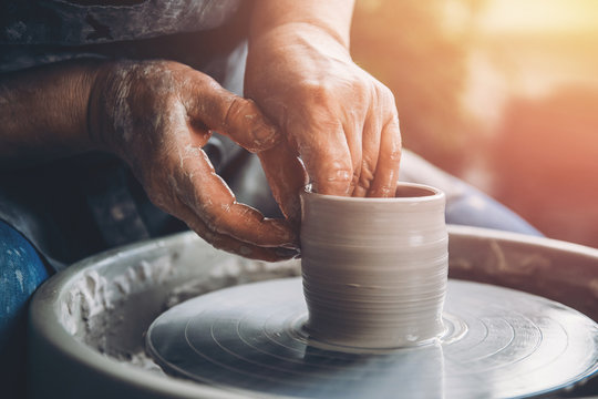 Wrinkled hands wizard on potter wheel makes clay dishes. Place to work