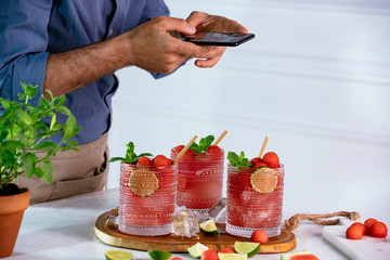 Food blogger using smartphone taking photo of beautiful watermelon cocktail on wood table to share on social media