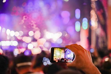 Close up of recording video with smartphone during a concert. colorful crowd on concert, disco night. - Image