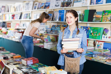 young woman with girl taking literature books in store with prints
