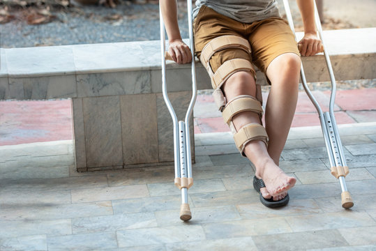 Part of disabled woman with crutches or walking stick or knee support sitting on marble bench
