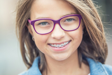 Portrait of happy young girl with dental braces and glasses Wall mural