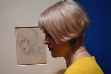 Royal Collection Trust staff pose beside preparatory sketches of Leonardo Da Vinci's The Last Supper at A Life in Drawing exhibition in London