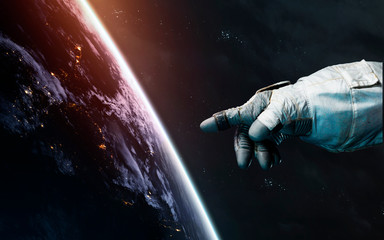 Wall Mural - Astronaut hand points to Earth planet. Awesome science fiction render. Elements of this image furnished by NASA