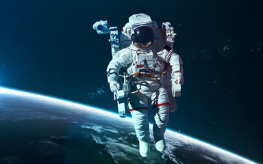 Wall Mural - Astronaut at Earth orbit. Science fiction wallpaper. Elements of this image furnished by NASA