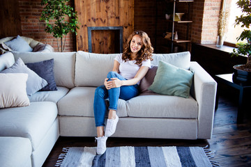 Wall Mural - Portrait of her she nice-looking attractive lovely charming stylish cheerful cheery lady sitting on comfortable sofa at industrial loft wooden brick style interior room