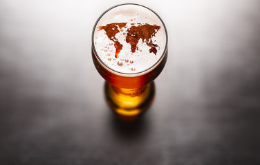 world map silhouette on foam in beer glass on black table. The continents shapes are altered ones from visibleearth.nasa.gov