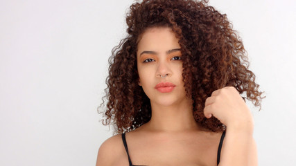 hair blowing closeup portrait of mixed race model with freckles slightly smiling Touches her curly hair