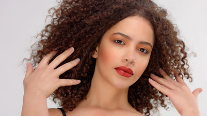 hair blowing closeup portrait of mixed race model with freckles touches her hair