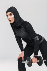 Woman fitness muslim posing isolated over white wall background make exercises with dumbbell.
