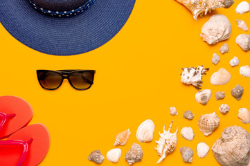 Wall Mural - Summer beach sea accessories. Coral flip flops, blue straw hat, sunglasses, shells, starfish on yellow background top view flat lay copy space. Summer background. Holiday vacation travel concept.